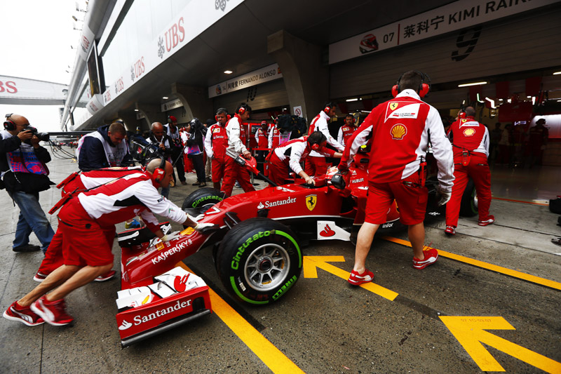 Raikkonen is pushed back into the garage during practice